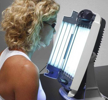 Face Tanning Lamp Used By Blonde Woman