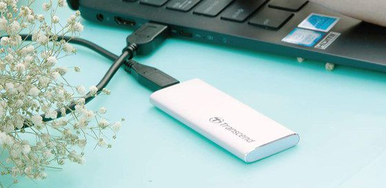 USB SSD Drive In White Plugged In Notebook