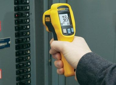 Compact Infrared Thermometer With Laser In Man's Hand