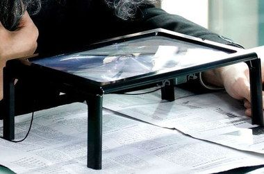 Magnifying Glass On Stand Above Newspaper